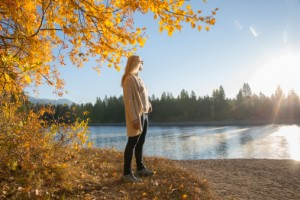 Woman watches sun rising over lake, autumn